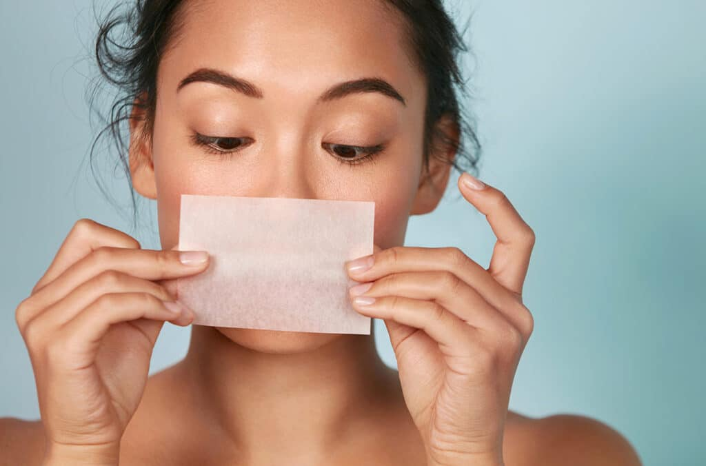 Woman Using Blotting Paper to Determine Skin Type